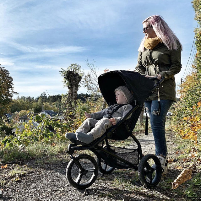 MB mini urban stroller with mother and child out for a walk on a park trail