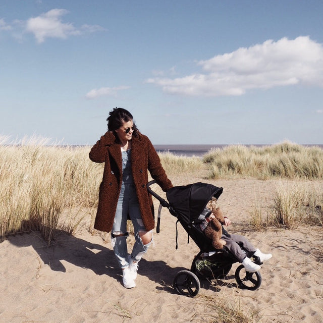 MB mini stroller on a sandy beach amongst the dunes with a mother and child enjoying a sunny day