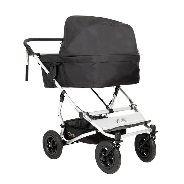 carrycot plus for twins installed on a Mountain Buggy duet double stroller shown from front side angle with sun hood up in place_black_black