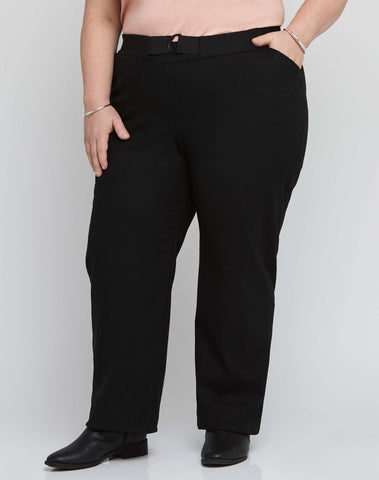 Front view of size 18 model wearing black stretch plus size work pants with an adjustable waist.