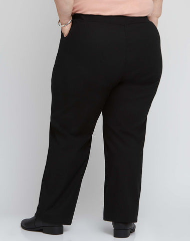 Back view of size 18 model wearing black stretch plus size work pants with an adjustable waist.