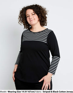 front view of size 14 model is wearing a womens plus size top in black cotton jersey with black and grey striped sleeve and yoke details.