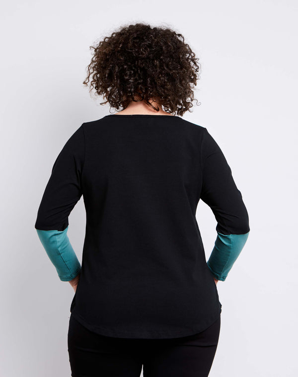 Back view of size 14 model is wearing a womens plus size top in black cotton jersey with sage sleeve and yoke details