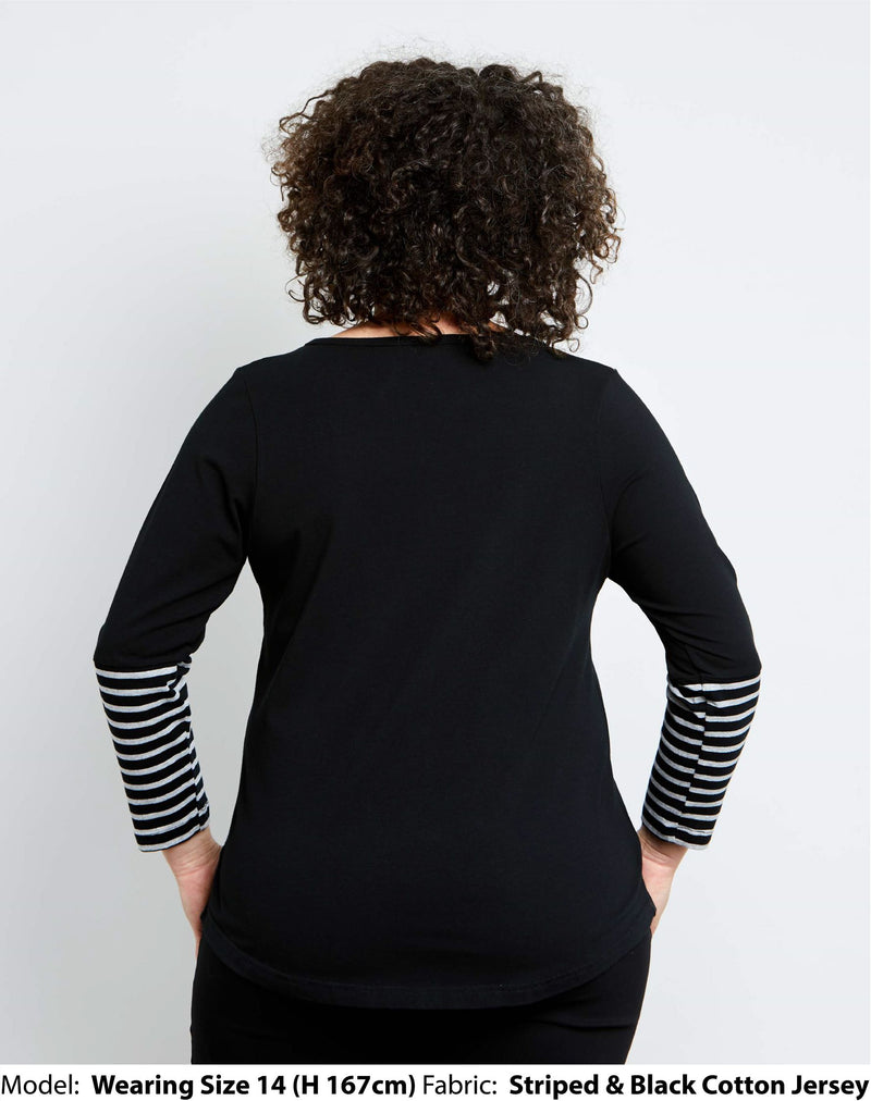 Back view of size 14 model is wearing a womens plus size top in black cotton jersey with black and grey striped sleeve and yoke details.