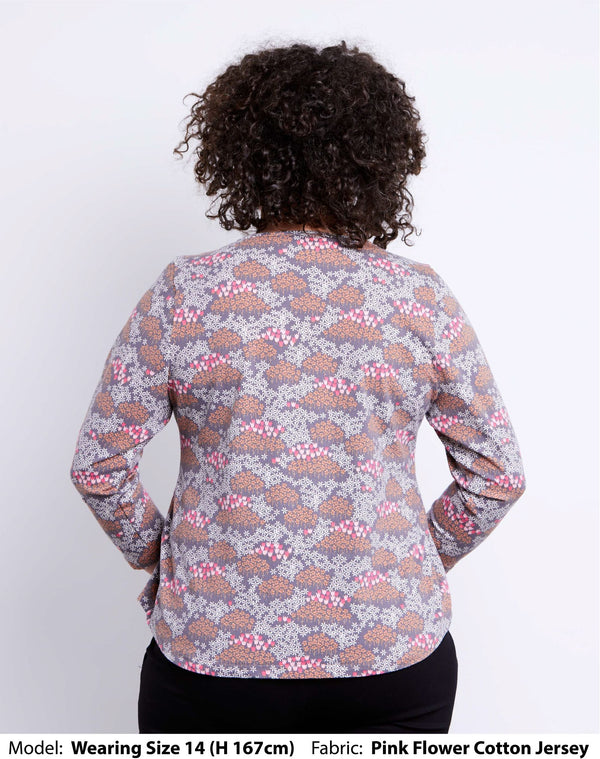 Back view of size 14 model wearing a womens plus size top with long sleeves in cotton jersey with small pink flowers printed on it.