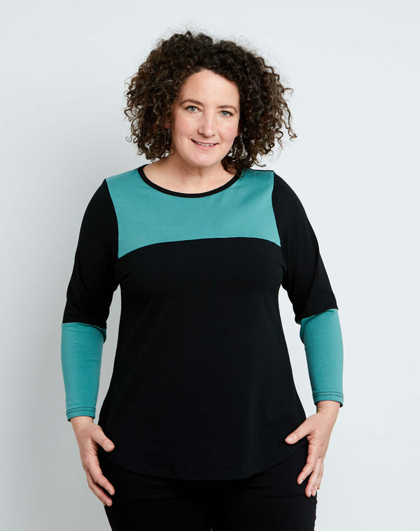 Front view of size 14 model is wearing a womens plus size top in black cotton jersey with sage sleeve and yoke details.