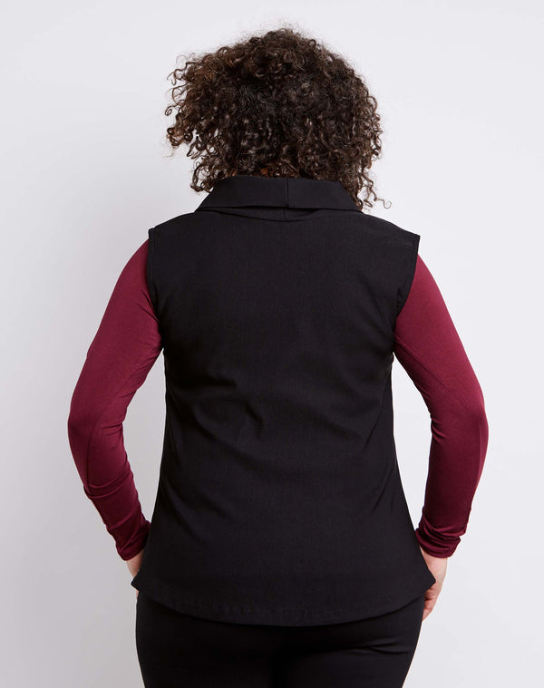 Back view of size 14 model dressed for work in a womens plus size vest with collar in black stretch ottoman.
