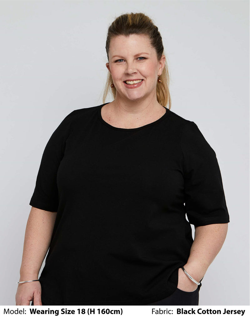 Front view of size 18 model wearing a womens plus size top with short elbow length sleeves in plain black cotton jersey.