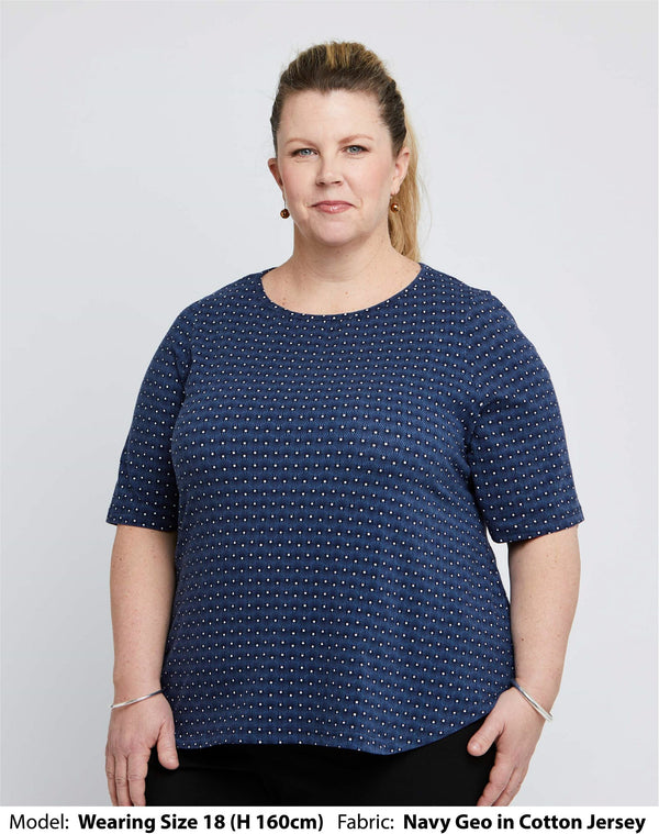 Front view of size 18 model wearing a womens plus size top with short elbow length sleeves in cotton jersey with a small navy geo pattern printed on it.