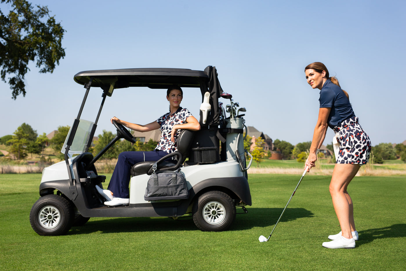 Two females on golf course, one in cart and the other hitting a golf ball