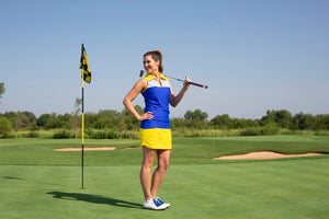 Girl standing next to hole on golf course with her club, posing in golf attire