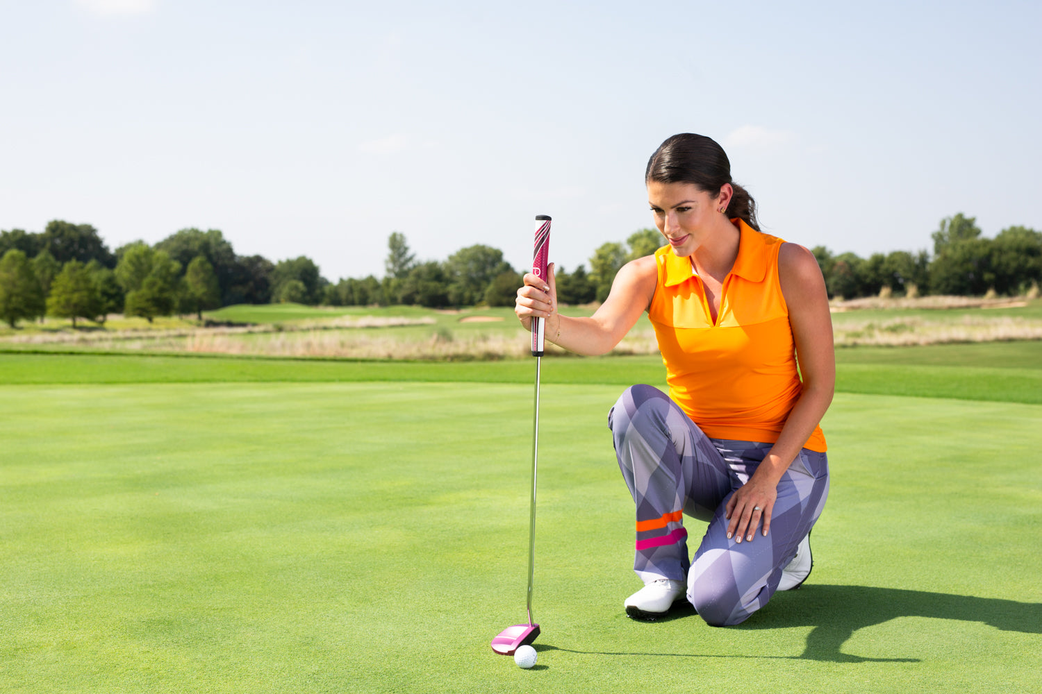 Woman on golf course studying putt