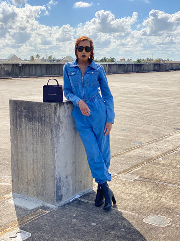 a women wearing a mid wash blue denim zipper jumpsuit with black boots and a black bag