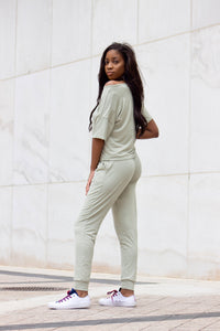 A woman showing the side view of a sage green jogger set. The shirt is drop down a little from her shoulder and matching jogger pants with side pockets.