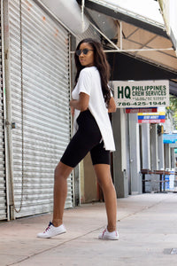 A model wearing an oversize white tee shirt and showing the side view of black biker shorts (cycling shorts) while standing in front of a store.