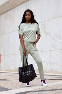 A woman wearing sage green two piece loungewear set. A flowy short sleeve top and jogger pants with pockets. She is holding a black This is Me Boutique tote bag.