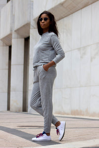 A women wearing a grey crew neck long sleeve shirt with grey joggers as a loungewear set.