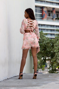 A woman showing the back of pink floral mini dress with a tie back and long sleeves.