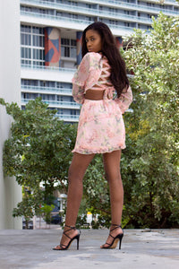 A woman showing the side and back view of pink floral long sleeve mini dress with chiffon frill.