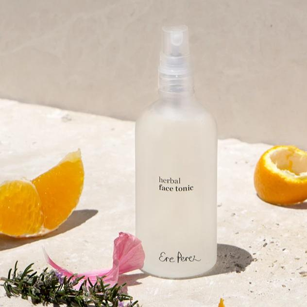 Bottle of Ere Perez Herbal Face Tonic with slices of mandarin orange, rose petal and rosemary sprig.