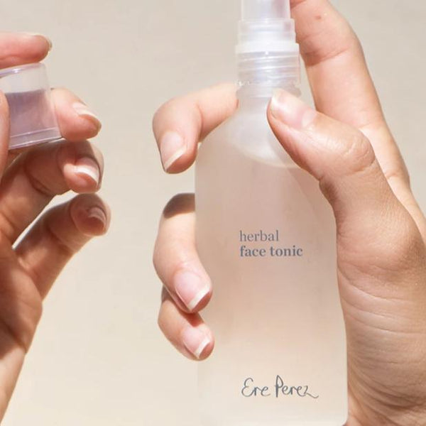 Two hands holding and spraying a bottle of Ere Perez Herbal Face Tonic