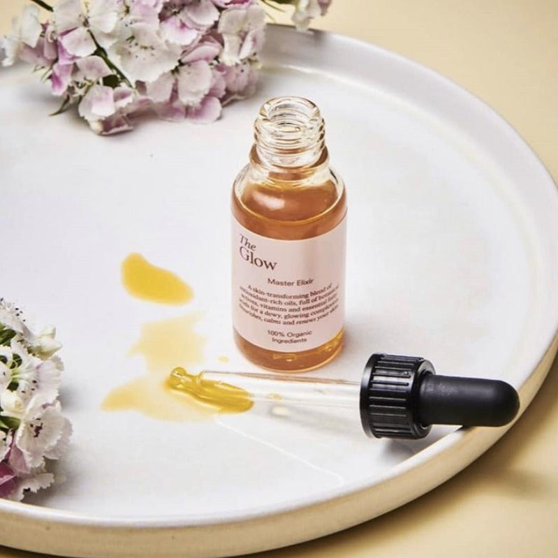 The Glow Master Elixir open bottle on tray with flowers