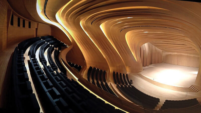 A large wooden auditorium with curving wood panels designed to be acoustically beneficial.