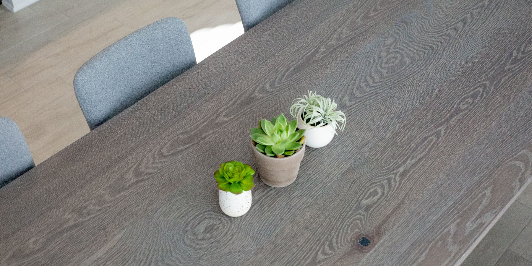 Cerused wood dining table with three small succulents sitting on top of the table