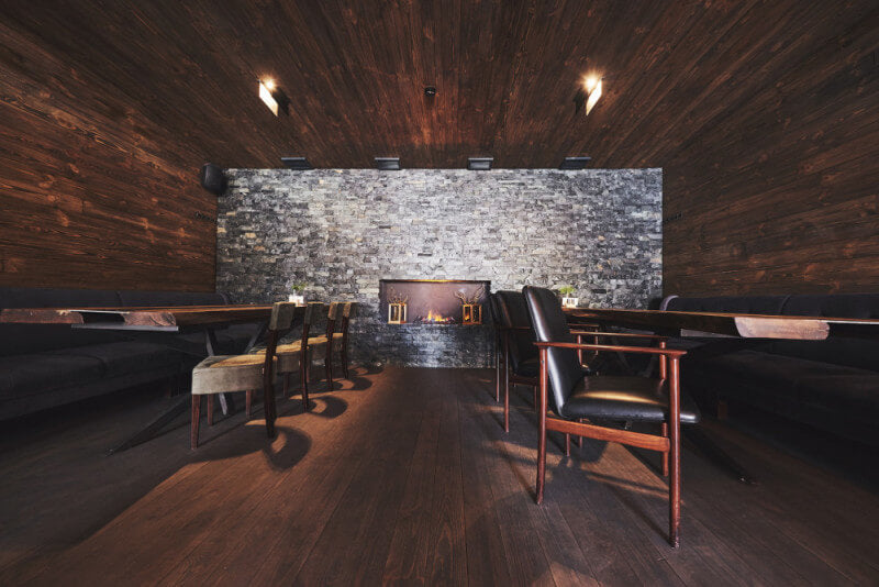 A moody restaurant dining room with wood floors, walls, and ceiling with a masonry accent wall.