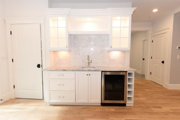Wet bar with natural hardwood flooring