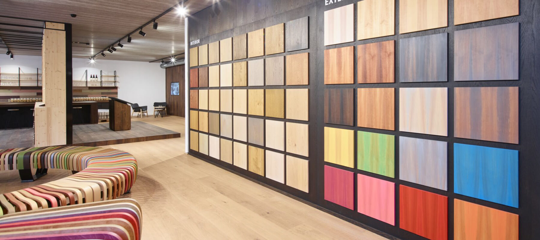 A wall showing color tiles of the Rubio Monocoat interior and exterior colors with a bench and other decor in the background