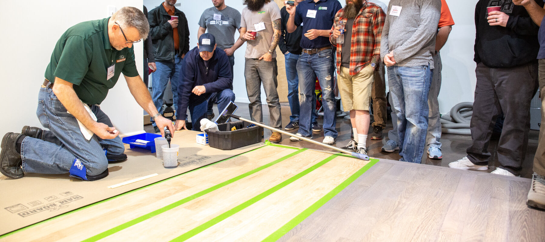 An instructor kneeling on hardwood flooring while teaching a group of men how to finish the hardwood flooring