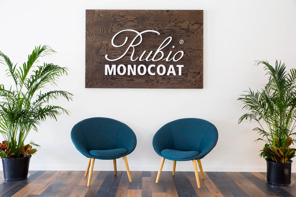 Two chairs on a hardwood floor with plants on either side of the chairs against a white wall in the Rubio Monocoat USA headquarters