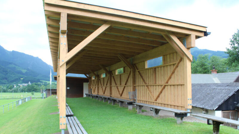 A long wooden covering for outdoor gatherings.