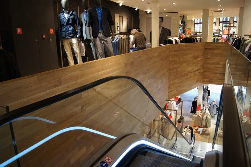 Escalator in clothing store with wood accent wall finished with hardwax oil.