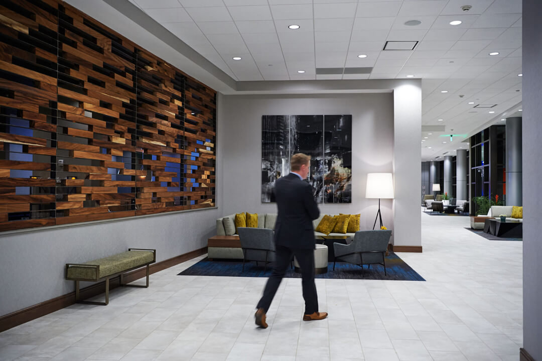 Man walking through hotel lobby with wood accent wall to his left.