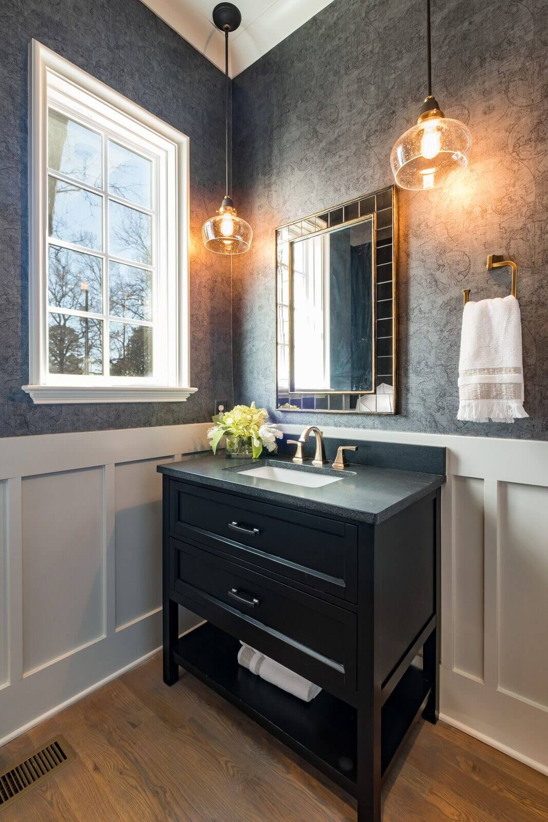 Beautifully designed guest bathroom with hardwood flooring and a dark vanity.