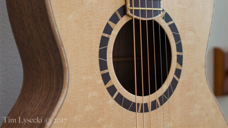 The soundhole in a birdseye maple acoustic guitar with Oil Plus 2C wood finish.