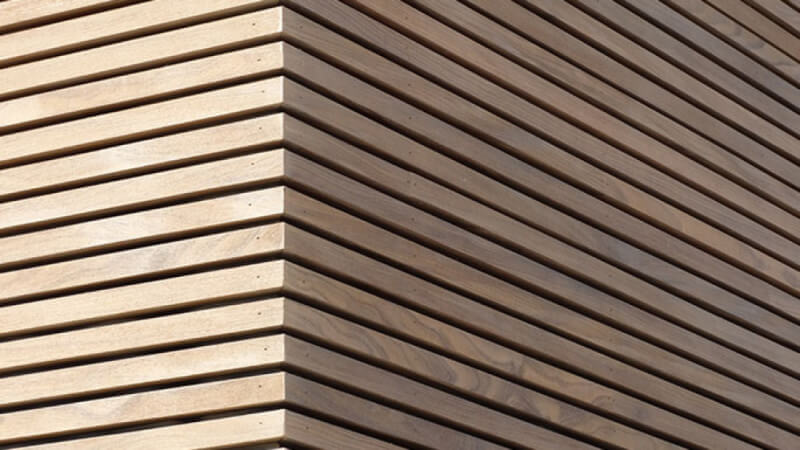 The corner of a wood facade finished using Hybrid Wood Protector.