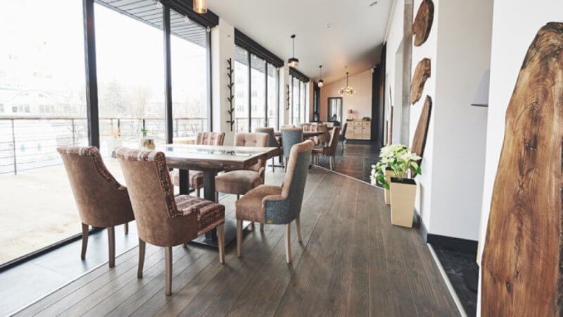 A rustic restaurant dining area with wood floors and wood cookie artwork on the walls.