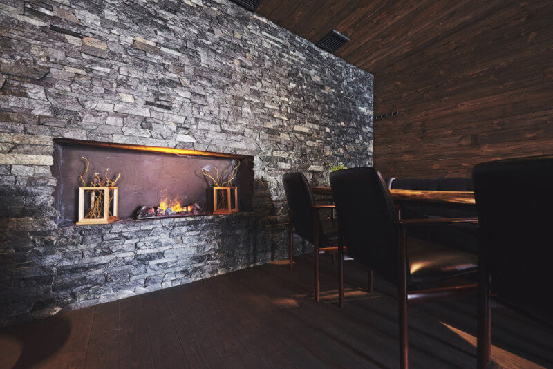 A moody restaurant dining room with wood floors, walls, and ceiling with a stone accent wall.