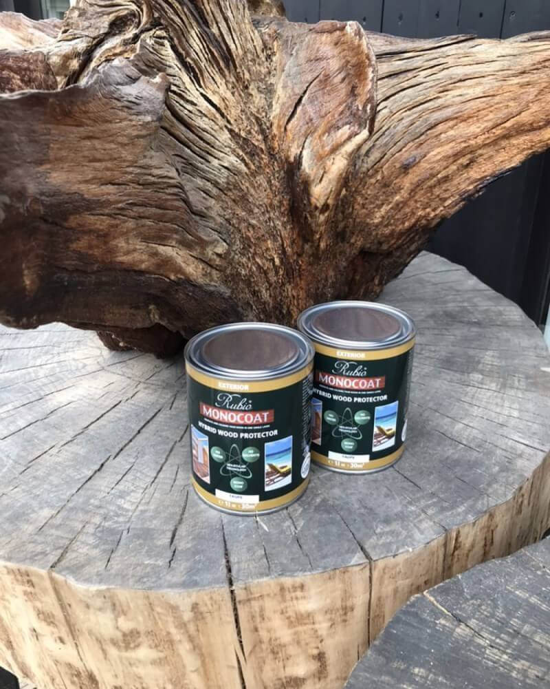 Rubio Monocoat Hybrid Wood Protector cans sitting on a tree stump outside.