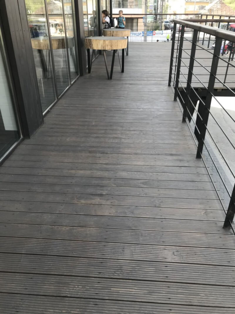 Wood patio at a restaurant with cable railing and wood tables.