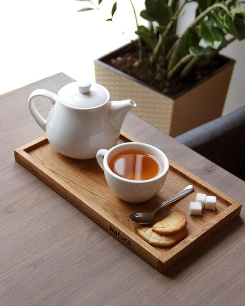 A serving tray with tea and cookies sitting on a matte finished wood table in a restaurant.