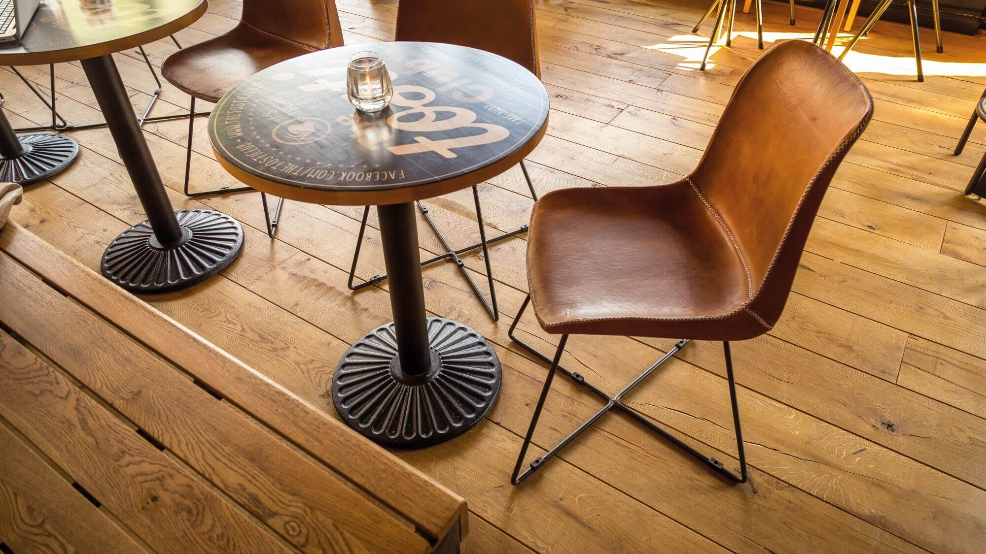 A small table with a leather chair at it on an aged oak floor.