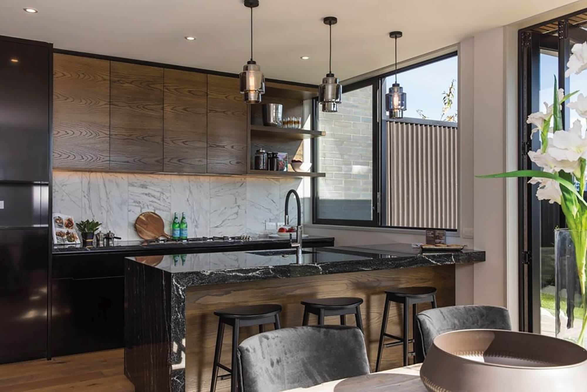 Warm kitchen designed with brown wood cabinets and dark marbled counters.