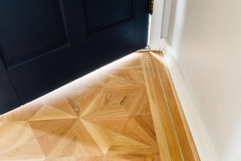 Detail of a solid white oak parquet inlay floor with brass border.