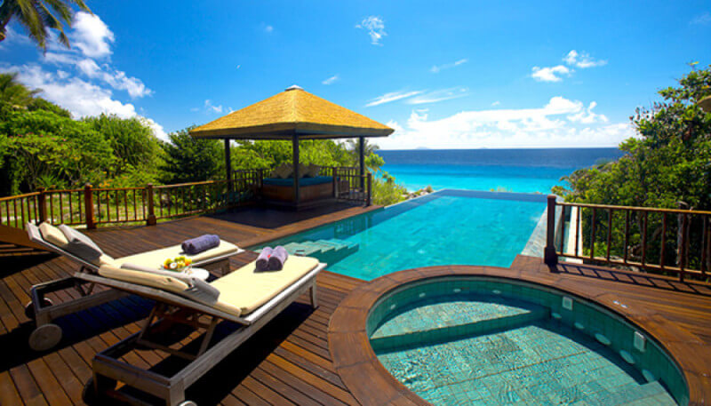 A luxury tropical resort hardwood deck and infinity pool.