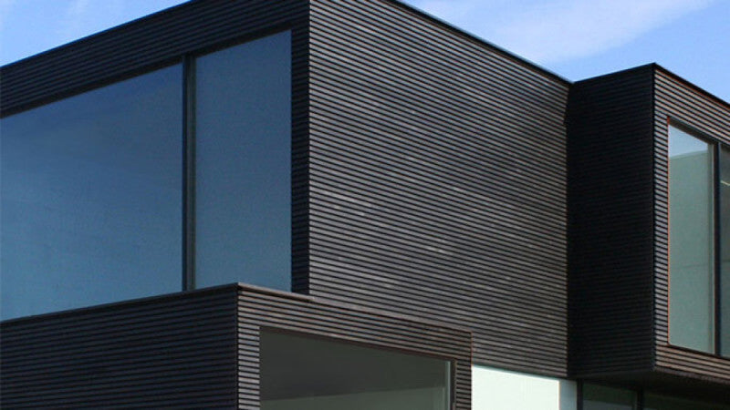 A modern home with dark exterior wood siding.