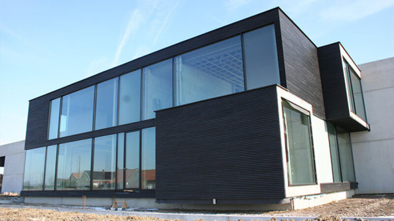 The entire side of a modern home finished with glass paneling and wood siding.